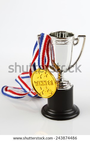 Medal and trophy on plain background - stock photo