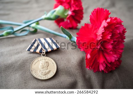 Medal For Victory over Germany in the Great Patriotic War of 1941-1945 and two red carnations. Still life dedicated to Victory Day. 9 May. - stock photo