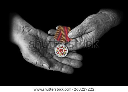 "Medal ""70 years of Victory in great Patriotic war 1941-1945"" in the hands of an elderly person - stock photo"