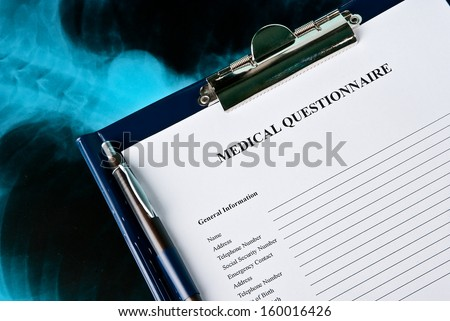 Medial Questionnaire in a clipboard on Xray photo of lungs