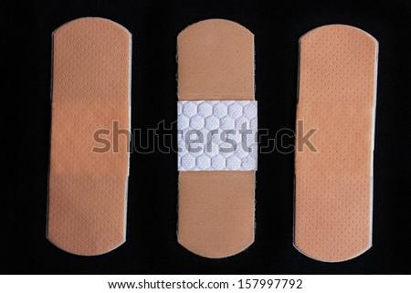 Medical adhesive bandage on black background - stock photo