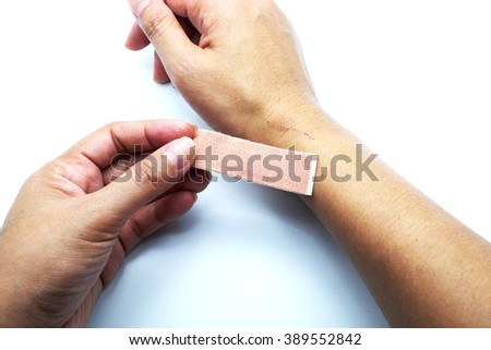 Medical/adhesive plaster for wound on female hand/wrist on white-blue background.