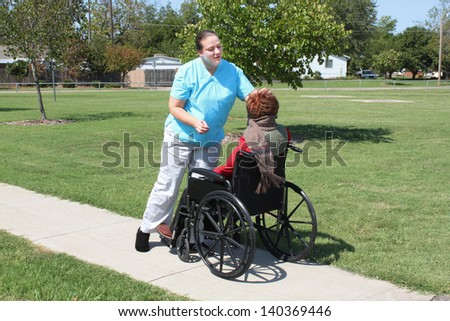 Medical aid helps a person in a chair - stock photo