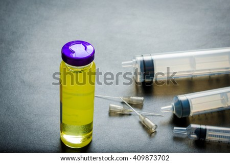 medical ampoules and syringe on black table - stock photo