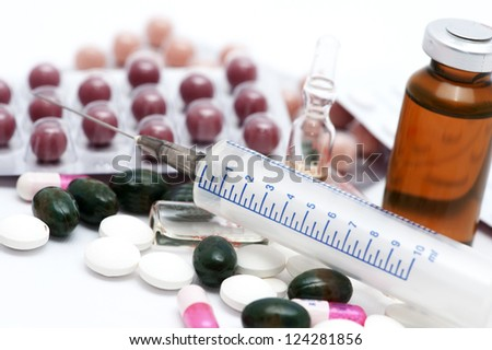 Medical ampoules, syringe and pills isolated on white - stock photo
