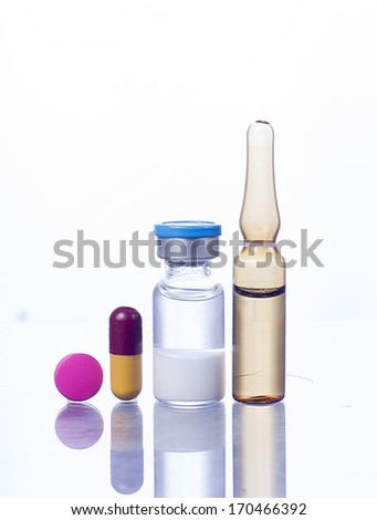 Medical ampules, syringe and pills isolated on white