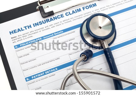 Medical and health insurance claim form with stethoscope on clipboard - stock photo