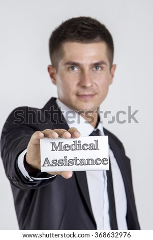Medical Assistance - Young businessman holding a white card with text - vertical image - stock photo
