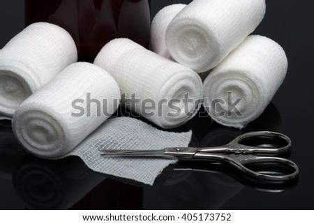 Medical bandage with scissors on black background - stock photo