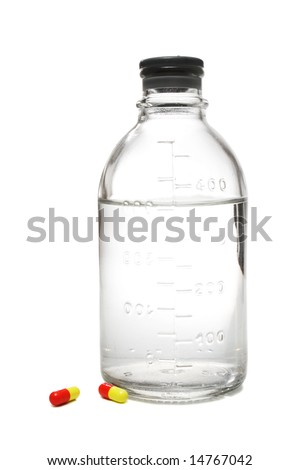 Medical bottle with physiologic saline and red-and-yellow pills beside it, isolated, on white background