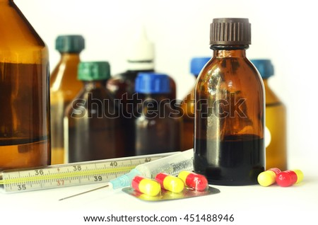 Medical bottles for mixtures, syrups and health-care oils with hypodermic and thermometer on white background - stock photo