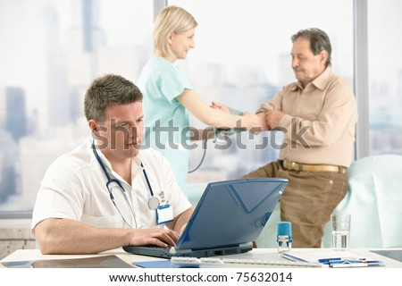 Medical checkup in doctor's office, doctor working with laptop, nurse in background measuring patient blood pressure.? - stock photo