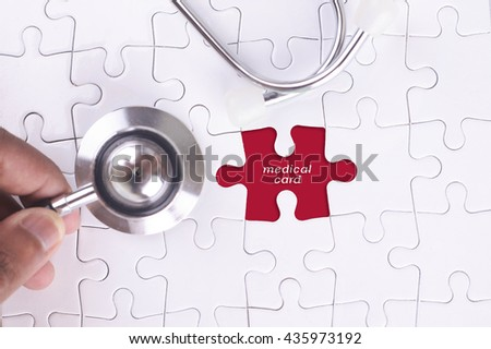 Medical Concept - A doctor holding a Stethoscope on missing puzzle with medical card WORD - stock photo