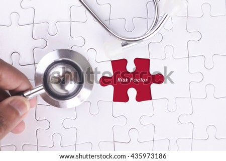 Medical Concept - A doctor holding a Stethoscope on missing puzzle with Risk Factor WORD - stock photo