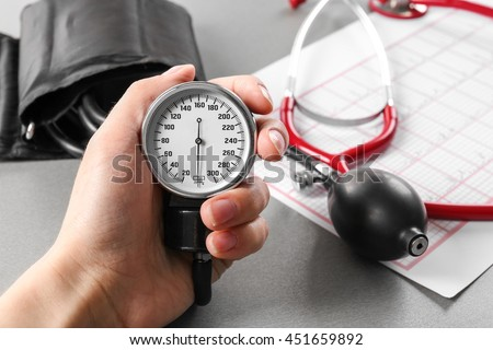 Medical concept. Hand holding medical manometer and cardiogram on background