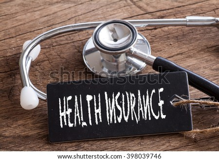 Medical Concept-Health Insurance words written on label tag with Stethoscope on wood background - stock photo