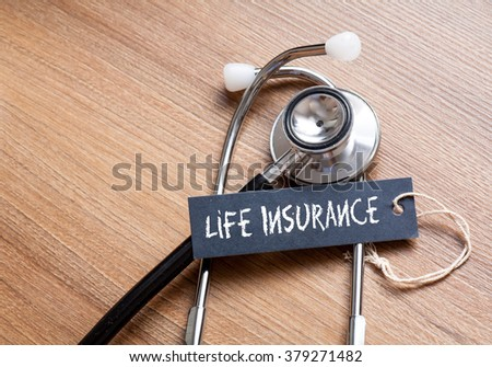 Medical Concept-Life Insurance word written on label tag with Stethoscope on wood background - stock photo