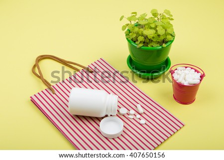 Medical concept - many different pills in a pink bucket, striped shopping bag and container of pills on yellow background - stock photo