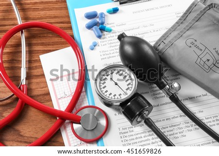 Medical concept. Medical stethoscope and manometer with patient history, close up - stock photo