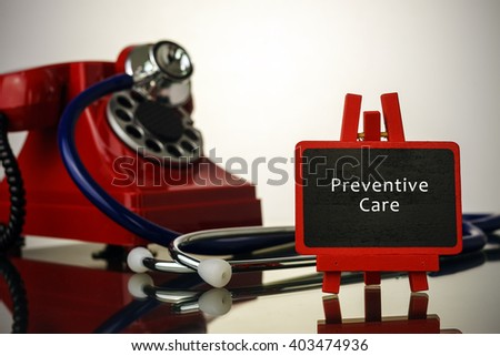 Medical concept.Phone and stethoscope on the table with PREVENTIVE CARE words on the board. - stock photo