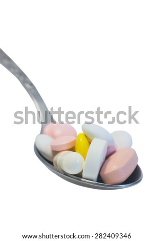 Medical concept: spoon piled with colorful pills  isolated on white. - stock photo