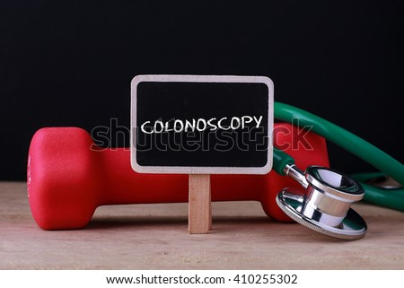 Medical concept - Stethoscope and dumbbell on wood with Colonoscopy words - stock photo