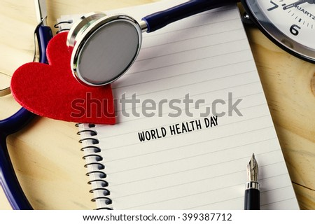 Medical concept. Stethoscope, heart shape, notepad, clock and pen on wooden table with WORLD HEALTH DAY words.