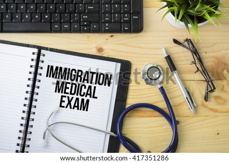 Medical Concept - Stethoscope with notebook written Immigration Medical Exam with keyboard, green plant, a pen and spectacle on wooden background - stock photo