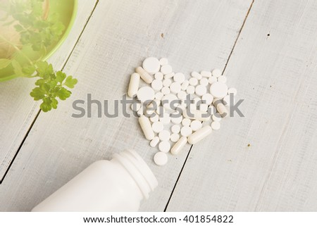 Medical concept - white heart of pills and capsules on white wooden desk - stock photo