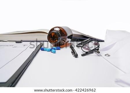 Medical doctor.Book,medicine,doctors apron,prescription pen and glasses on white background. - stock photo