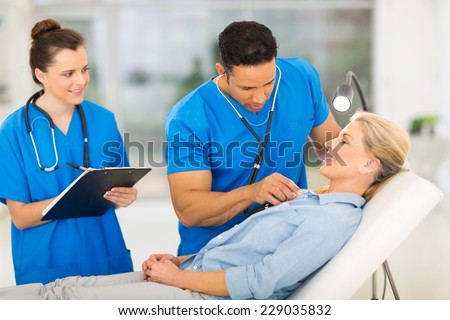 medical doctor examining senior patient in office - stock photo