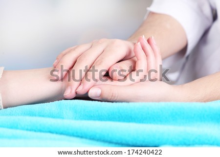Medical doctor holding hand of patient, on light background - stock photo