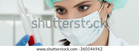 Medical doctor in protective gloves and surgical mask and hat comparing two flasks with dark red liquid in laboratory. Scientific research, healthcare and medical concept. Letter box format - stock photo