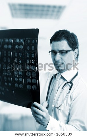 Medical doctor is examining a computer tomograph image. - stock photo