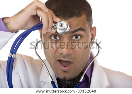 Medical doctor looks astonished, while examining his head with stethoscope. Isolated on white. - stock photo