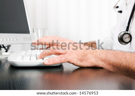 Medical Doctor (only hands to be seen) doing administrative stuff at his computer