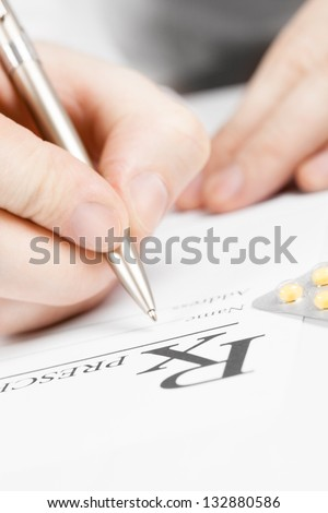 Medical doctor signing prescription with  silver pen on a table - stock photo