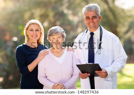 medical doctor standing with senior patient and her daughter outdoors - stock photo
