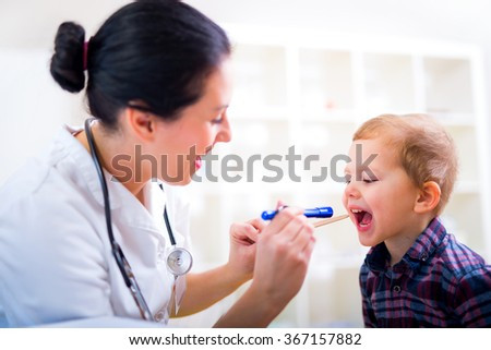Medical doctor with child in office. Pediatrician examining little boy's throat with tongue depressor - stock photo