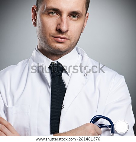 Medical doctor with stethoscope portrait against grey background  - stock photo