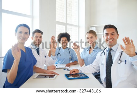 medical education, health care, gesture, people and medicine concept - group of happy doctors meeting and waving hands at hospital - stock photo