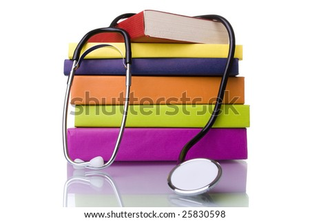 medical equipment and a stack of books isolated on white (selective focus) - stock photo