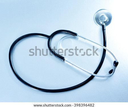 Medical equipment, stethoscope on a blue toned background.
