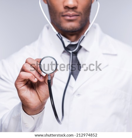 Medical exam. Cropped image of confident African doctor stretching out his stethoscope while standing against grey background - stock photo