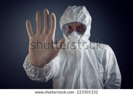 Medical Health Care Worker Showing Stop Sign with hand, entrance is forbidden in quarantine zone. - stock photo