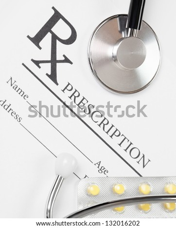 Medical ideas - blank prescription with pills and stethoscope above it - stock photo