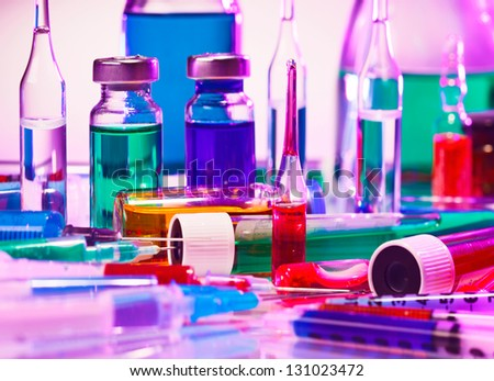 Medical laboratory glass equipment still life on blue purple - stock photo