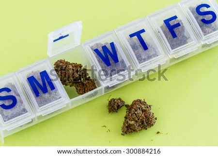 Medical marijuana buds in daily pill organizer sitting on green background - stock photo