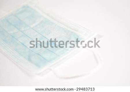 Medical mask on white surface - stock photo
