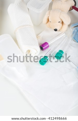 Medical means for taking blood analysis at babies. Soother,toy rattle,plush dog,test tube,white towels in a background.